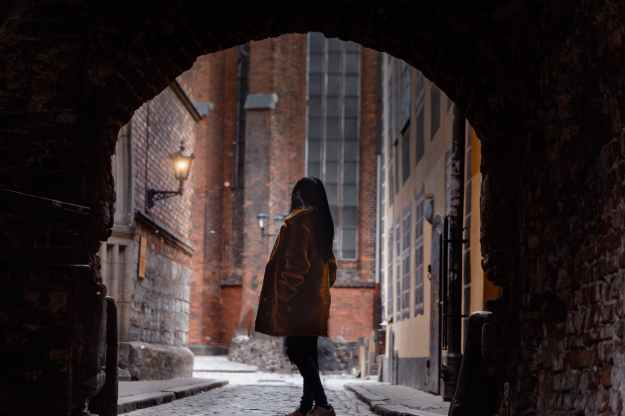 woman standing inside alley tunnel