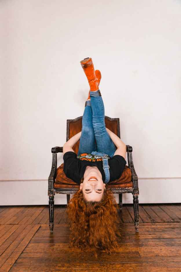 photo of inverted woman on wooden chair